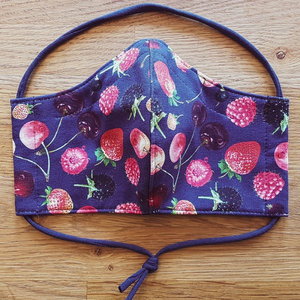 Fabric facemask with red fruit on deep blue background