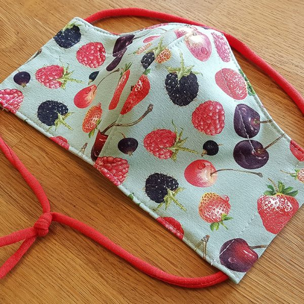 Fabric facemask with red fruit on mint background