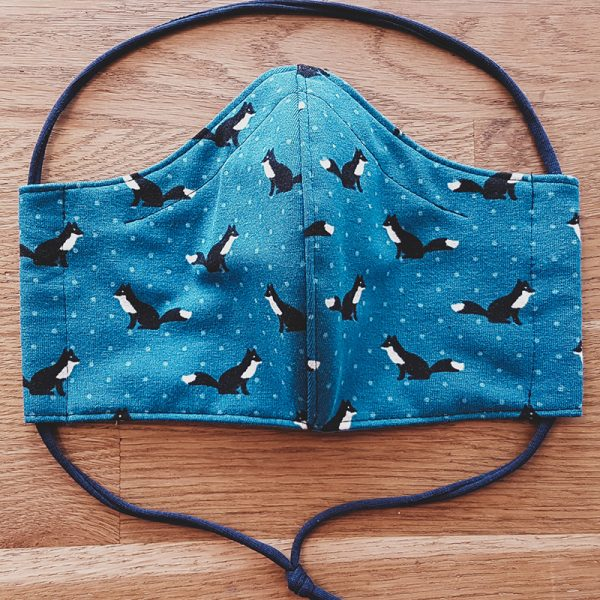 Fabric facemask autumn themed with black and white foxes on petrol blue background