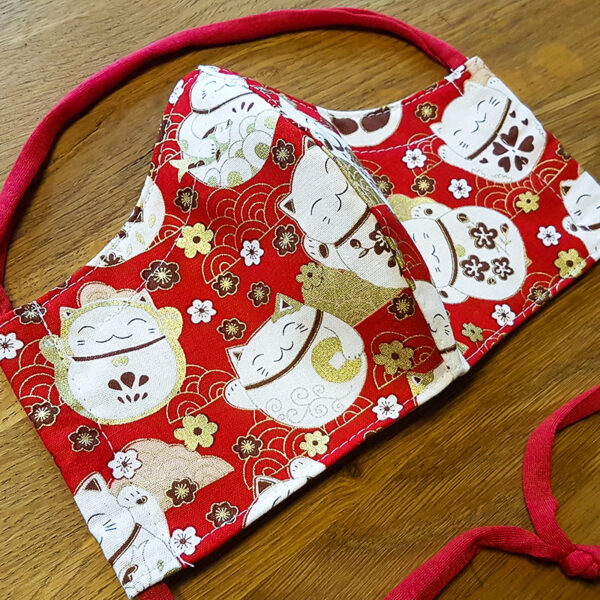Fabric facemask with lucky cats print on red background