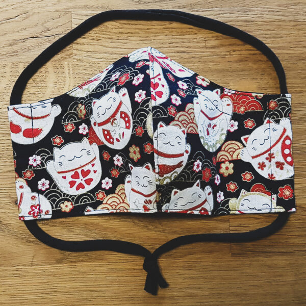 Fabric facemask with lucky cats print on black background